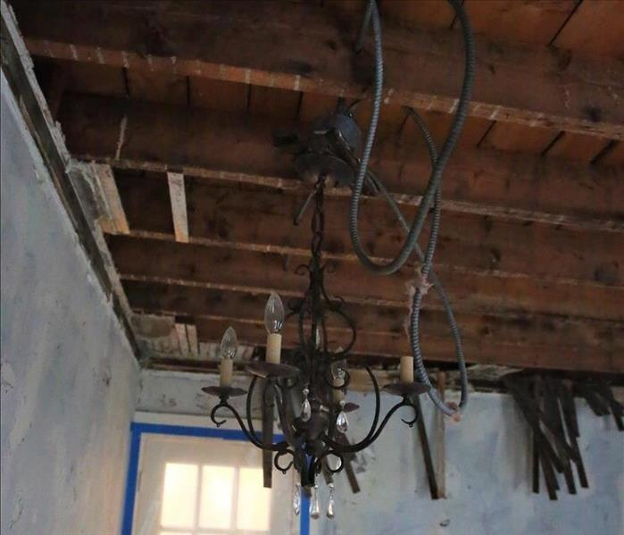 Chandelier hanging from ceiling before cleanup
