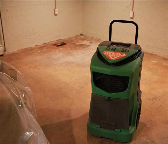A basement floor with a SERVPRO dryer