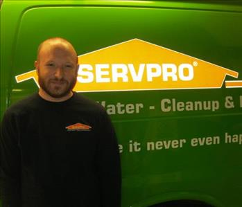 Bearded SERVPRO employee standing in front of a SERVPRO van while wearing a SERVPRO sweatshirt.