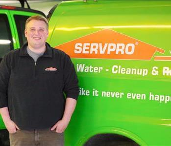 Image of male SERVPRO employee standing in front of SERVPRO poster and office items