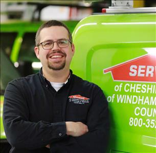Male SERVPRO employee with dark hair and facial hair wearing a SERVPRO jacket and glasses standing in front of a SERVPRO van