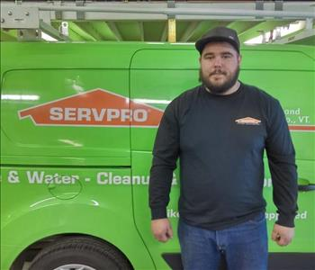 Male bearded SERVPRO employee wearing a SERVPRO sweatshirt, hat and jeans standing in front of a SERVPRO van