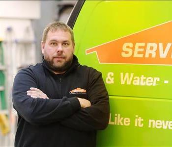 A man standing in front of a green SERVPRO van