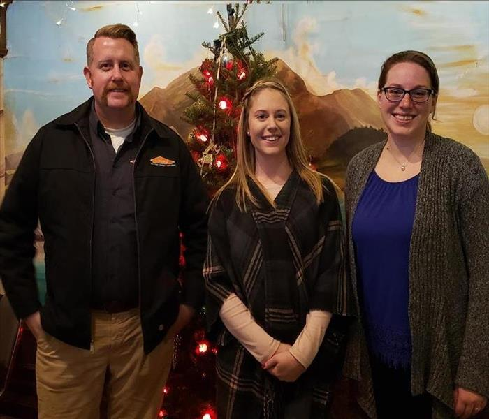 a man and two women standing in front of a Christmas tree and a wall mural smiling