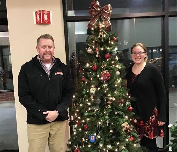 a man and a woman standing next to a Christmas tree