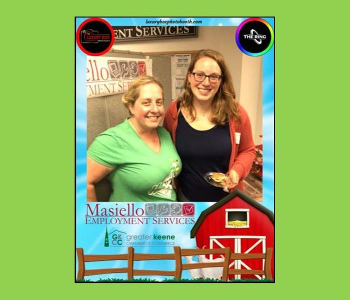 two women at networking event with frame around picture featuring branding graphics for affiliated companies from event.