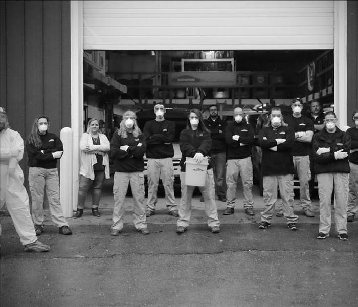 Black & white photo of an entire staff of employees standing in front of open overhead door of warehouse.