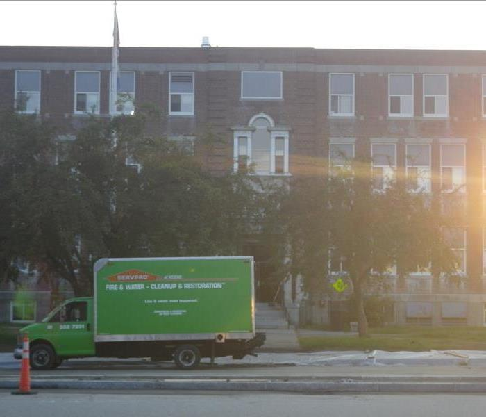 SERVPRO vehicle parked outside a brick educational facility