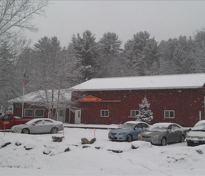 Wide shot of red commercial building in the middle of a snow storm with cars parked out front.