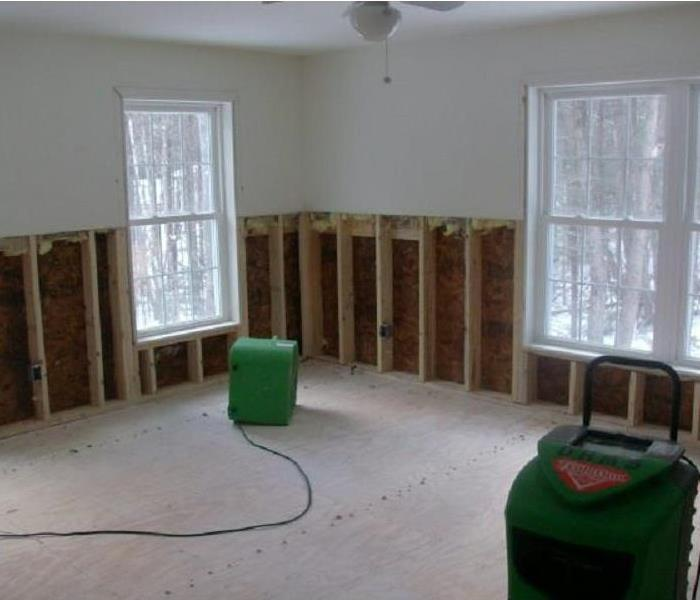 Room which has flooring and base of walls removed with two large dehumidifiers in the room to dry.