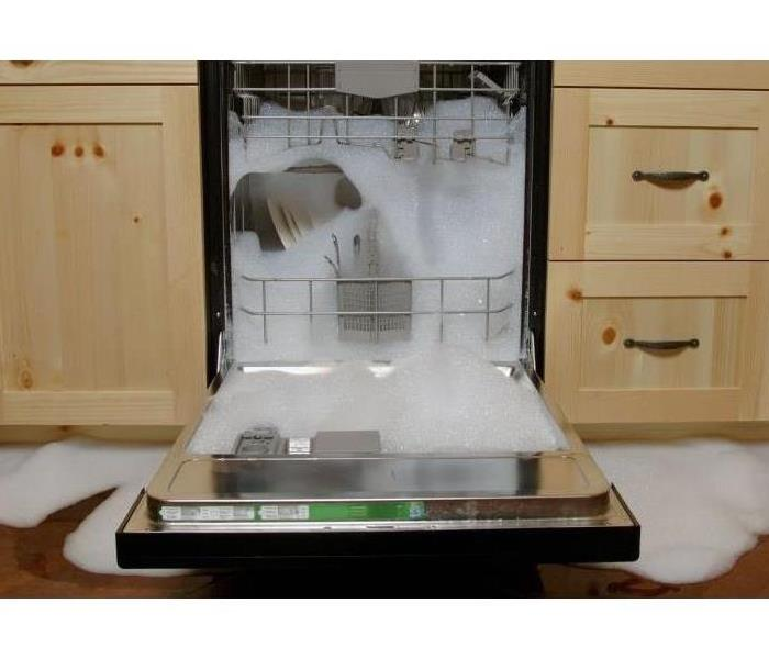 A dishwasher overflowing in a kitchen