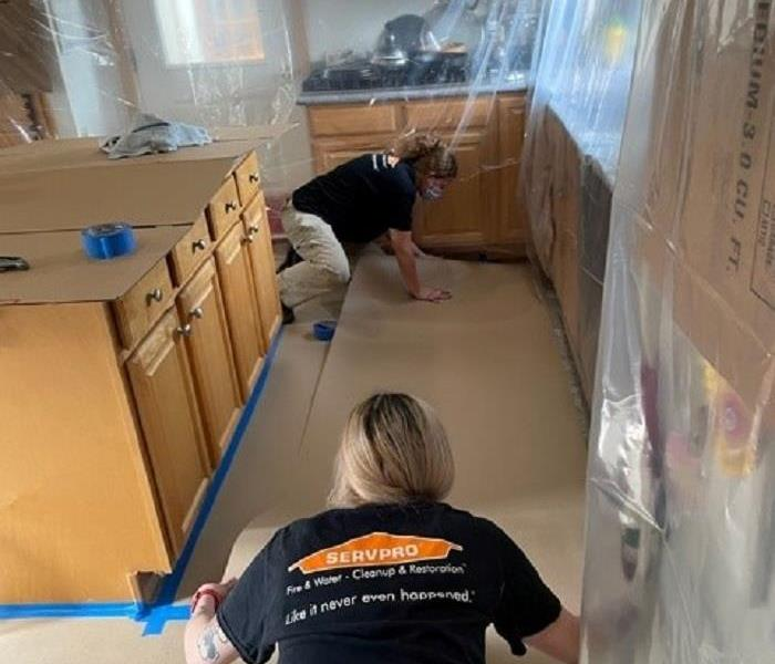 Two SERVPRO technicians carefully placing cardboard on top of kitchen floor. Countertops and cabinets have plastic over them.
